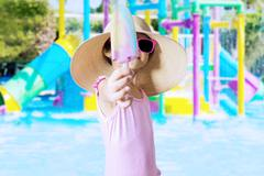 Child showing ice cream at pool - stock photo