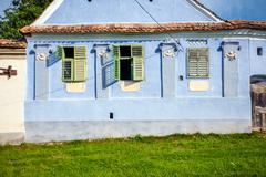 Viscri, Romania - June 23, 2013: Blue painted traditional house with green sh Stock Photos