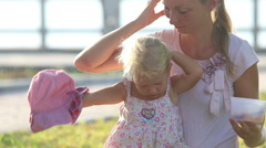 Long-haired mother sits with daughter on lawn at embankment Stock Footage