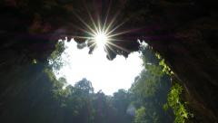 Bottom of deep hollow cave, looking up to sunstar shining through Stock Footage