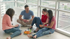 Friends sitting on the floor and eating an orange Stock Footage