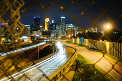 Chain link fence and view of I-35 and the skyline at night, seen from the 24t - stock photo