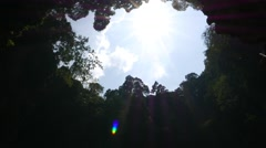 Blue sky and bright sun view from bottom of cave, ceiling gap opening Stock Footage