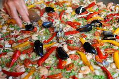 Chef adds a bit of parsley in rice paella with shrimp Stock Photos