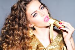 Portrait of alluring young girl with golden banana Stock Photos