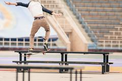 Teenager doing a trick by skateboard on a rail in skate park Stock Photos