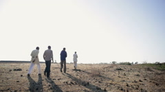 Indian village men walking on dry baron land, long shot Stock Footage