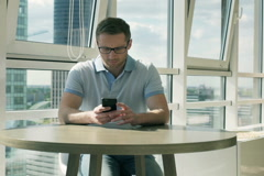 Man using cellphone at the table and going somewhere Stock Footage