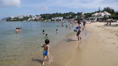 Children and adults relax on the Repulse Bay Beach,  Hong Kong Stock Footage