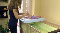 Mother make therapeutic foot massage for baby on swaddle board Stock Footage