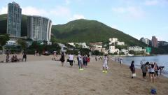 Children and adults relax on the Repulse Bay Beach in evening on a weekday, Stock Footage