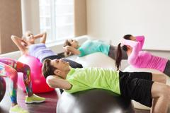 Happy people flexing abdominal muscles on fitball Stock Photos