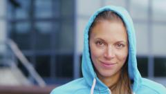 Portrait of a hooded female runner smiling to camera Stock Footage