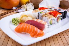 Appetizing sushi with wasabi, fruits and chopsticks Stock Photos