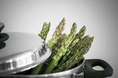 Green asparagus in metal pot with lid, selective focus - stock photo