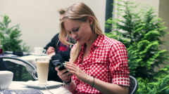 Girl talking on cellphone and eating mousse from coffee in the cafe Stock Footage