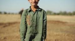 Village boy wearing a green shit in India, medium shot, shallow DOF - stock footage