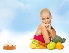 doubting woman with fruits and pie - stock photo