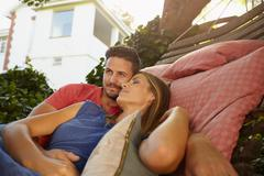Appreciative young couple relaxing on a hammock together - stock photo