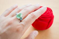 Hand on gem stone jewellery ring - stock photo