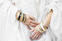 Girl hands with golden bracelets Stock Photos