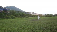 blonde girl in vietnamese poses in valley against train - stock footage