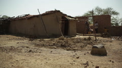 Poor family next to village house, India, long shot, shallow DOF - stock footage