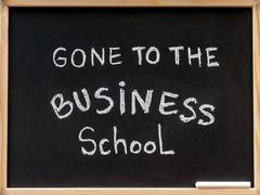 Gone to the business school message written with white chalk on blackboard - stock photo