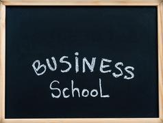 Business school message written with white chalk on wooden frame blackboard - stock photo