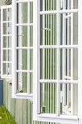 White wooden windows and green walls - traditional architecture in Norway - stock photo
