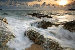 Sunset on the stones beach with motion wave, Phuket Stock Photos