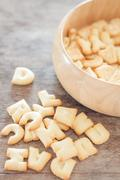 Alphabet biscuit in wooden tray - stock photo