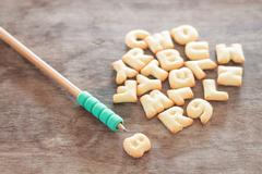 Alphabet biscuit on wooden table - stock photo