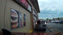 POV dashcam going through fast food drive through Stock Footage