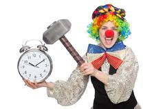Stock Photo of Female clown with alarm-clock and hammer isolated on white