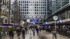 Commuters at rush hour with clocks in Docklands Stock Footage