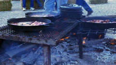 Mutton cooking in cast iron skillet over campfire at sheep camp in deser Stock Footage