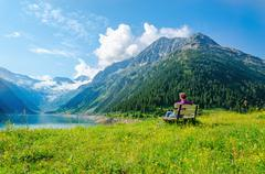 Woman sits on bench of azure mountain lake Austria Stock Photos