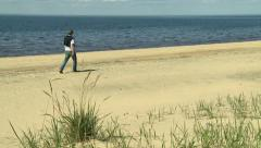 A young man walking on the beach and throwing stones into the water of the sea Stock Footage