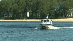 Boat passes along the coast and out to sea Stock Footage