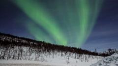 Northern light (aurora borealis) over a snowy mountain 4K Stock Footage