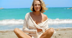 Blond Woman Sitting Crossed Legged on Beach - stock footage