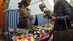 Young woman pay vendor for colorful sweets at candy store market Stock Footage