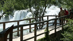 Visitors crossing the bridge and looking Krka waterfall Stock Footage