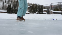 Girl ice skates and spins on ice covered pond Stock Footage