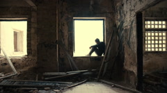 Hooded,troubled young man in wrecked abandoned building looking outside Stock Footage