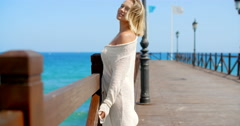 Blond Woman on Pier and Looking Back Over Shoulder Stock Footage