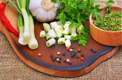 Green onion, garlic, parsley, chili pepper on cutting board - stock photo