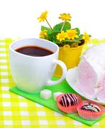 Cup of coffee with marshmallow, chocolate sweets, yellow wildflowers isolated - stock photo