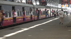 Passengers exit a commuter train at CTS in Mumbai, India Stock Footage